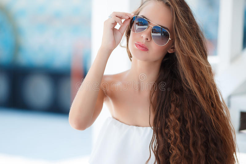 Summer portrait of a beautiful woman on the white steps. Young beautiful brunette woman with brown long hair,sun glasses,pink lipstick,attractive mole near lower royalty free stock photography