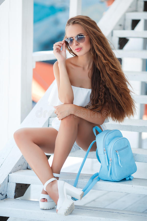Summer portrait of a beautiful woman on the white steps. Young beautiful brunette woman with long brown hair,sunglasses,pink lipstick,attractive mole near lower stock image