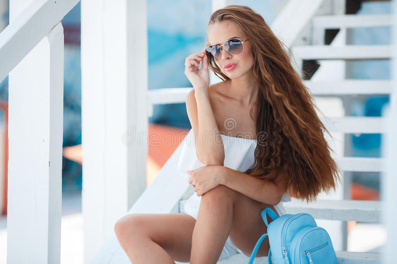 Summer portrait of a beautiful woman on the white steps. Young beautiful brunette woman with long brown hair,sunglasses,pink lipstick,attractive mole near lower stock photos
