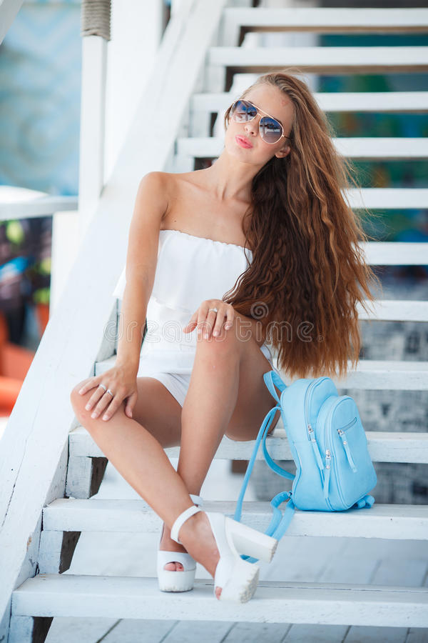Summer portrait of a beautiful woman on the white steps. Young beautiful brunette woman with long brown hair,sunglasses,pink lipstick,attractive mole near lower stock photography
