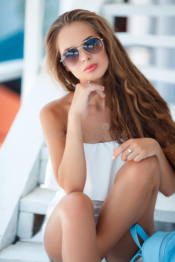 Summer portrait of a beautiful woman on the white steps. Young beautiful brunette woman with long brown hair,sunglasses,pink lipstick,attractive mole near lower royalty free stock photos