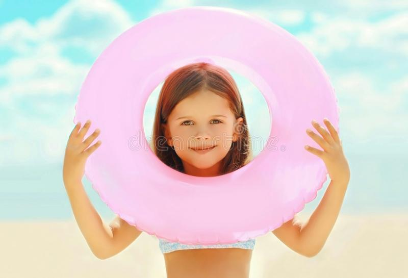 Summer portrait close-up little girl child with inflatable circle on summer beach royalty free stock photography