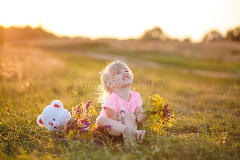 Summer portrait of a cute little girl playing with a teddy bear in the sunset. Portrait of a cute little girl playing with a teddy bear in a meadow at sunset royalty free stock photography