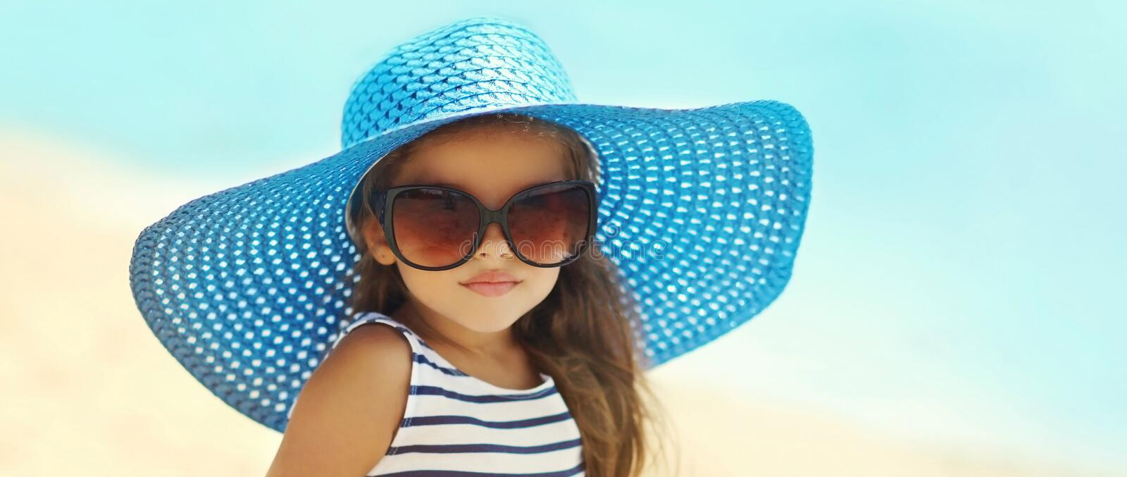 Summer portrait fashionable little girl in straw hat, sunglasses on beach stock photos