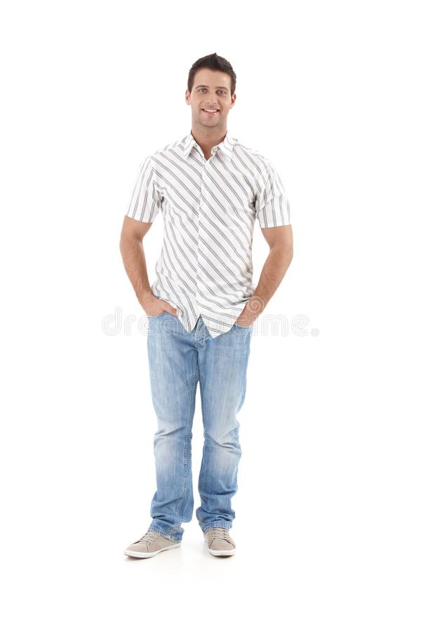 Summer portrait of goodlooking man. Standing in striped shirt, hands in pocket, smiling, cutout on white background royalty free stock photo