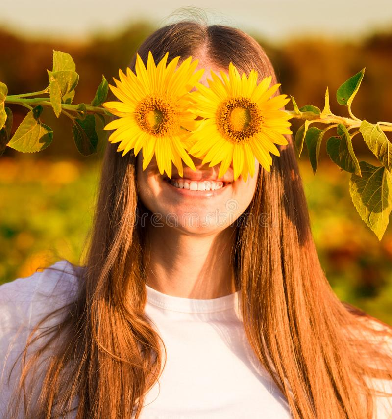 Summer portrait. Happy joyful girl with sunflower enjoying nature and laughing. On sunflower field royalty free stock image