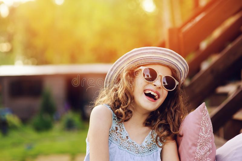 Summer portrait of happy kid girl on vacation in sunglasses and hat. Laugh and showing tongue royalty free stock photography