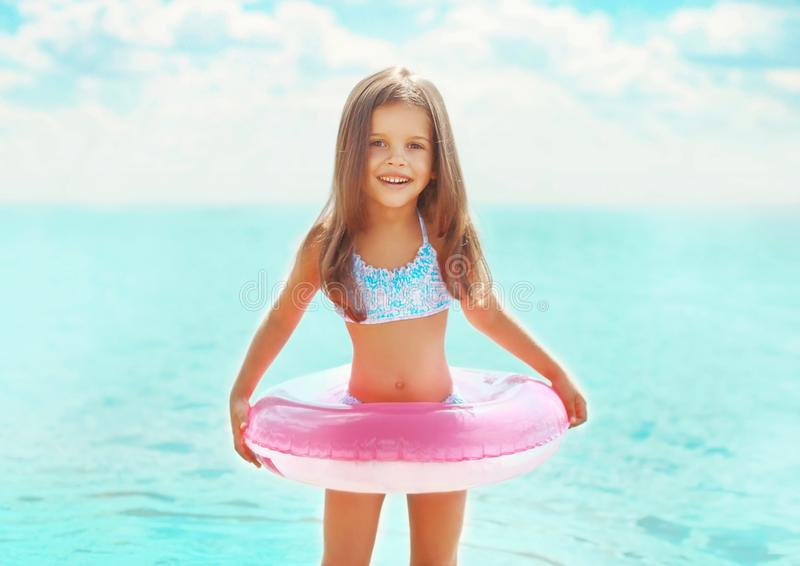 Summer portrait happy little girl child bathing with inflatable circle having fun royalty free stock photo