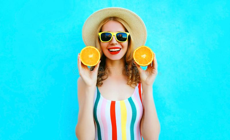 Summer portrait happy smiling woman holding in her hands two slices of orange fruit in straw hat on colorful blue stock photos