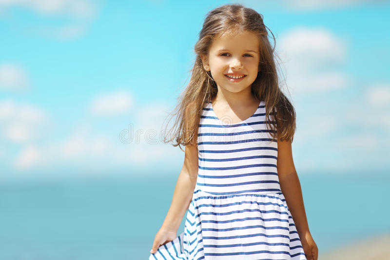 Summer portrait little girl in dress. On the beach royalty free stock image