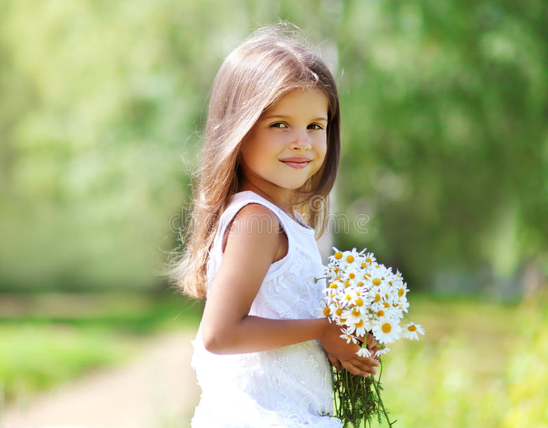 Summer portrait of little girl with flowers. In sunny day stock images