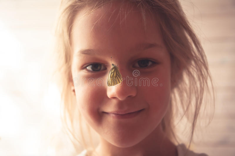 Summer portrait with smiling girl and butterfly on her nose symbolizing love to nature and kindness royalty free stock photo