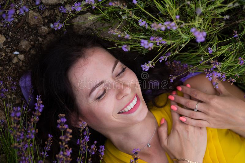 Summer portrait of young attractive woman in yellow dress lying in blooming violet lavander field stock image