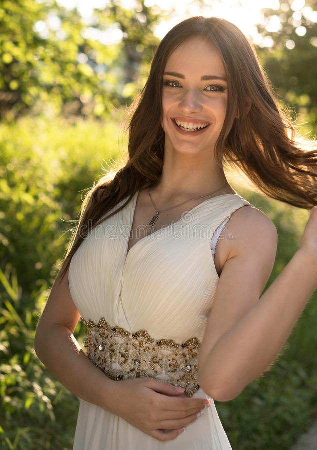 Summer portrait of young beautiful lady wearing long white evening dress posing in the park. royalty free stock photo