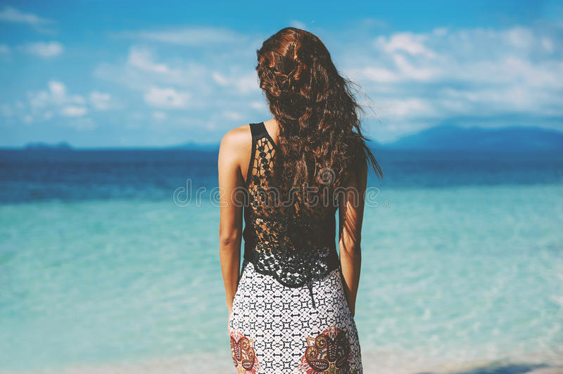 Summer portrait of young pretty woman looking at the ocean on a stock photo