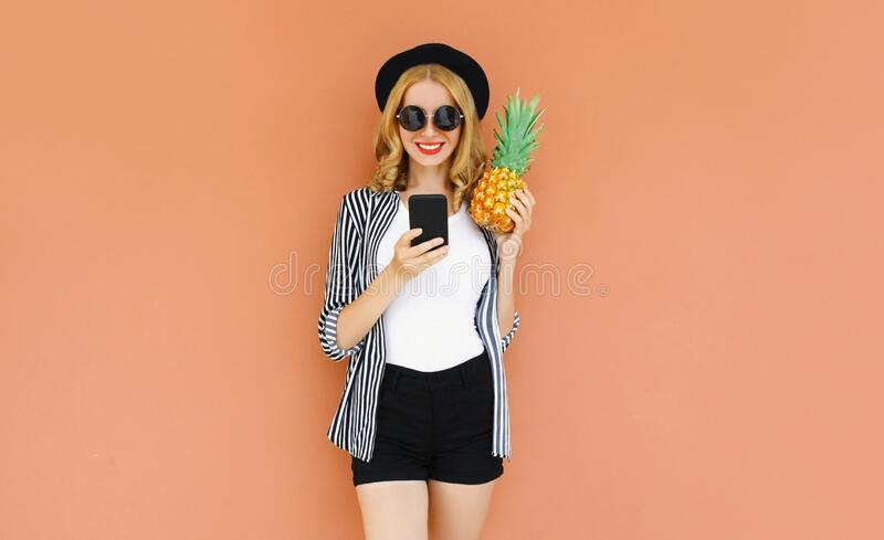Summer portrait of young smiling woman with smartphone and pineapple wearing a black hat, sunglasses, striped shirt stock image
