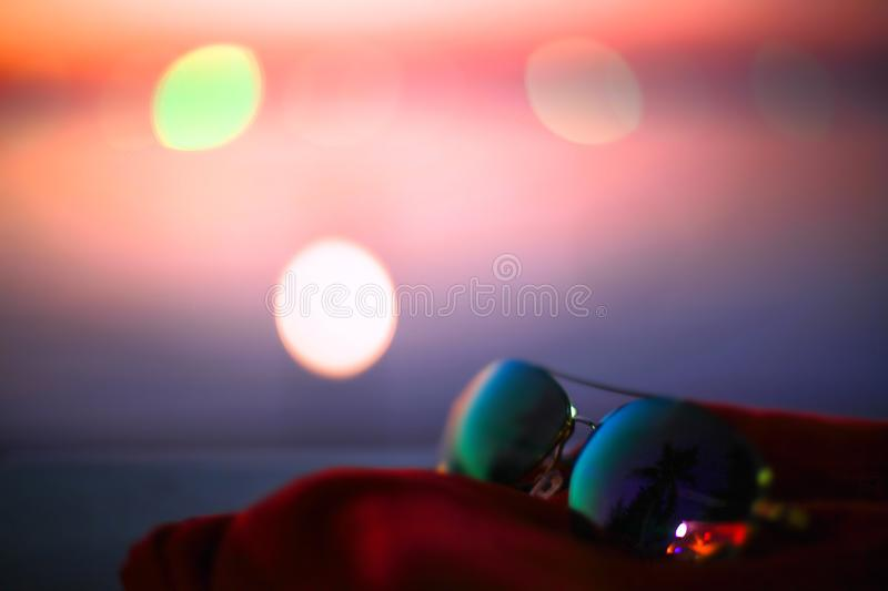 Summer poster with sunglasses, palms and bokeh effects. Blurred sunset beach background. stock images