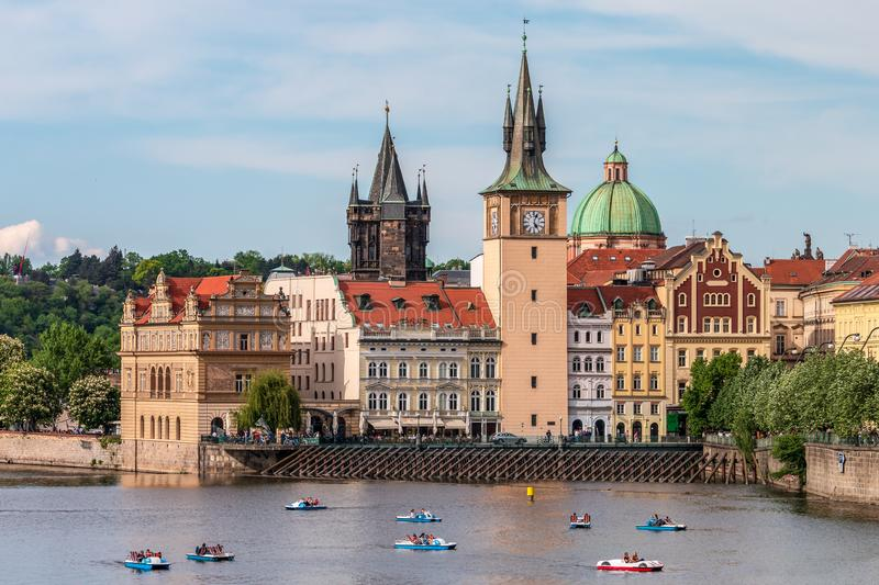 Summer Prague cityscape with touristic catamarans on Vltava river royalty free stock photography