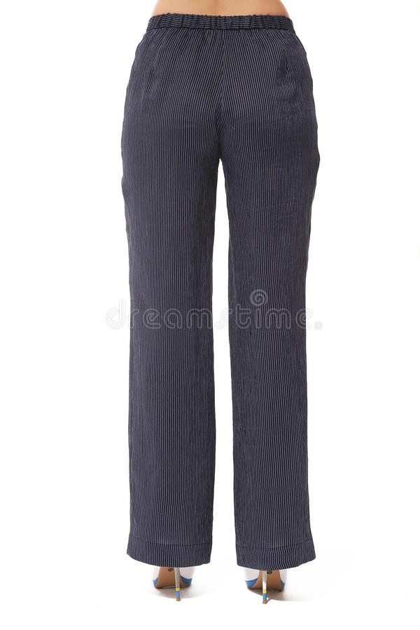 Dark blue bell loose trousers on model legs with white stiletto heels. Summer printed white cotton trousers on model legs with white stiletto heels back view stock images