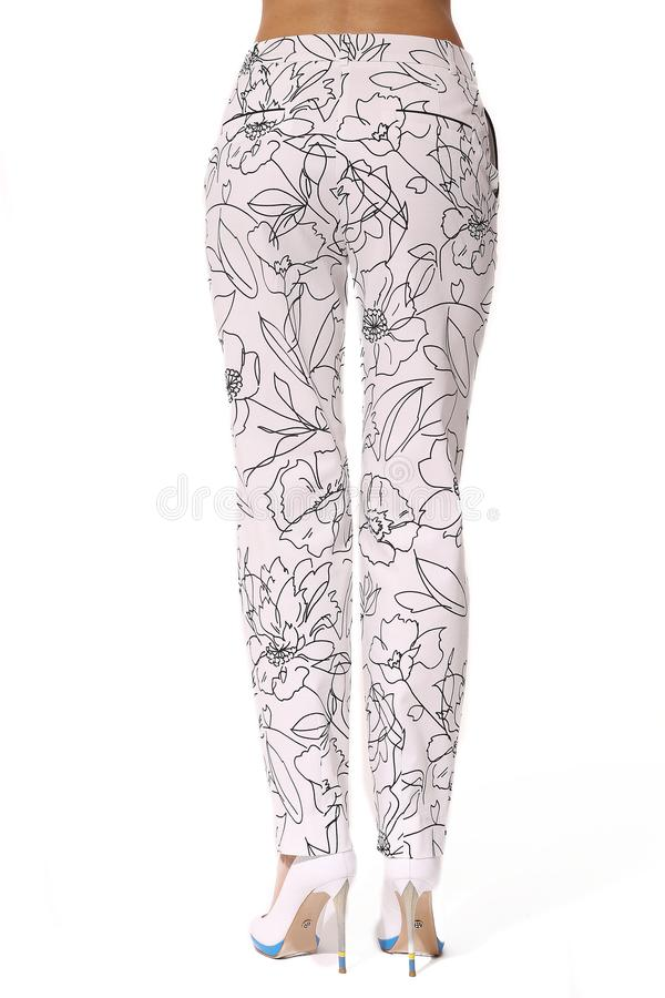 Summer printed white cotton trousers on model legs with white stiletto heels. With bare toes royalty free stock photos