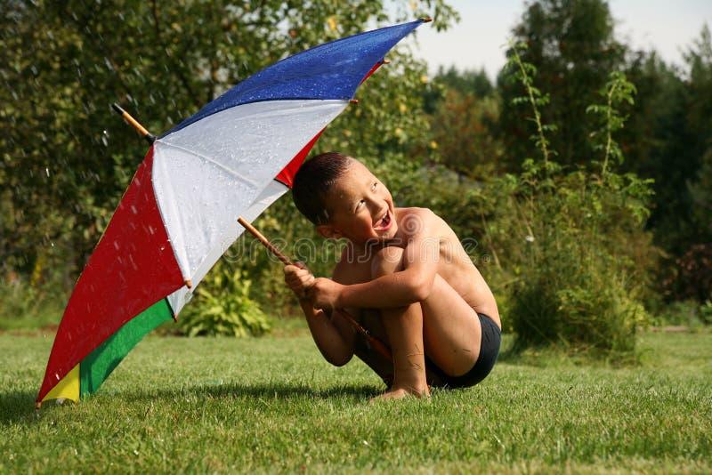 Summer rain. Little boy under umbrella in summer rain stock images