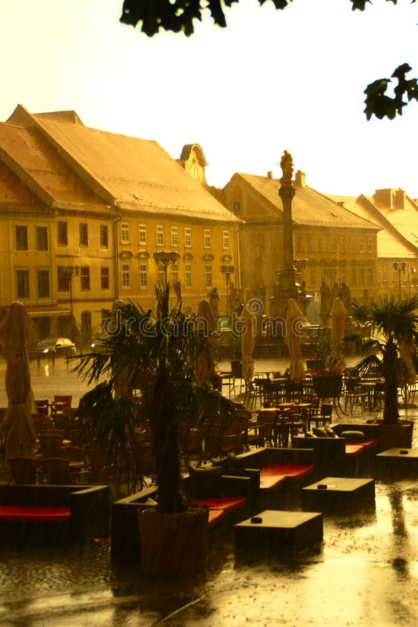 Summer Rain In The City. Summer rain and the sun on Main Square with open air caffee in historic center of Maribor, Slovenia stock images