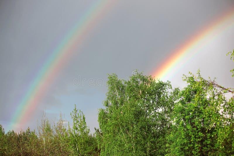 Summer rain and twin rainbow. In rural area stock photo