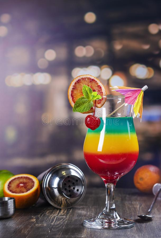 Summer rainbow layered cocktail. Glass of layered rainbow summer cocktail decorated with cherry and slice of red orange. Exotic summer drink on a bar counter stock photos