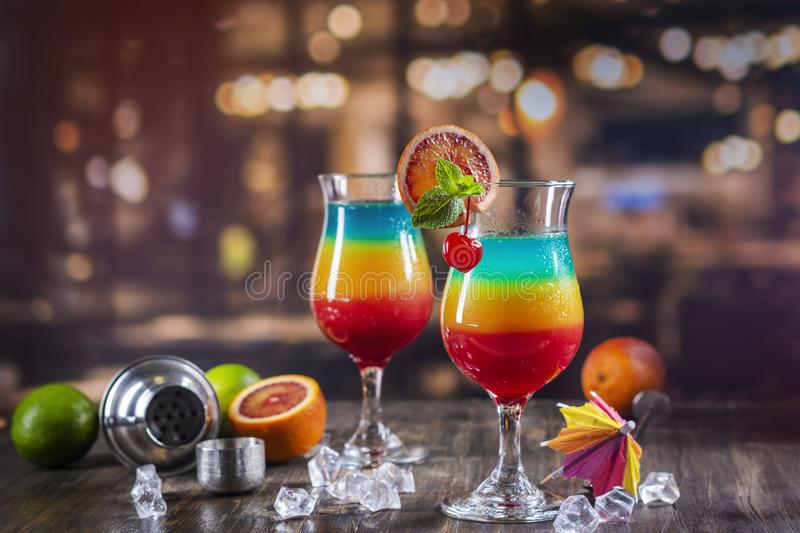 Summer rainbow layered cocktail. Glass of layered rainbow summer cocktail decorated with cherry and slice of red orange. Exotic summer drink on a bar counter royalty free stock image
