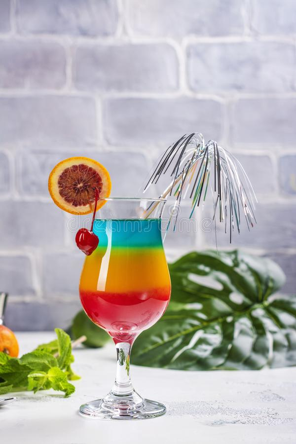 Summer rainbow layered cocktail. Glass of layered rainbow summer cocktail decorated with cherry and slice of red orange. Exotic summer drink. Copy space stock images