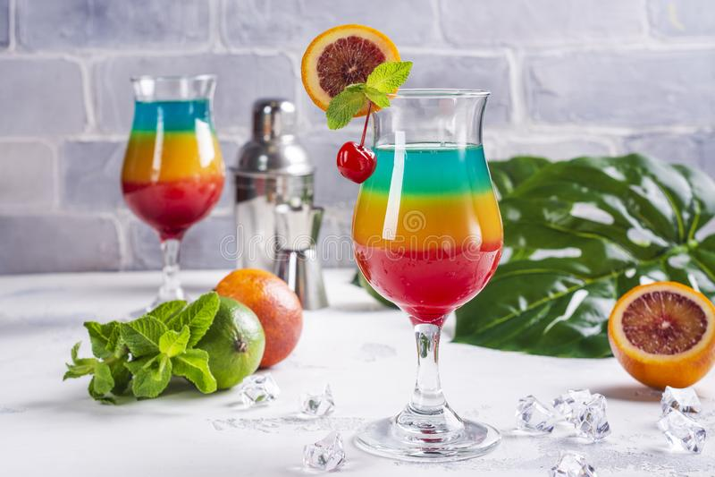 Summer rainbow layered cocktail. Glass of layered rainbow summer cocktail decorated with cherry and slice of red orange. Exotic summer drink. Copy space royalty free stock photo