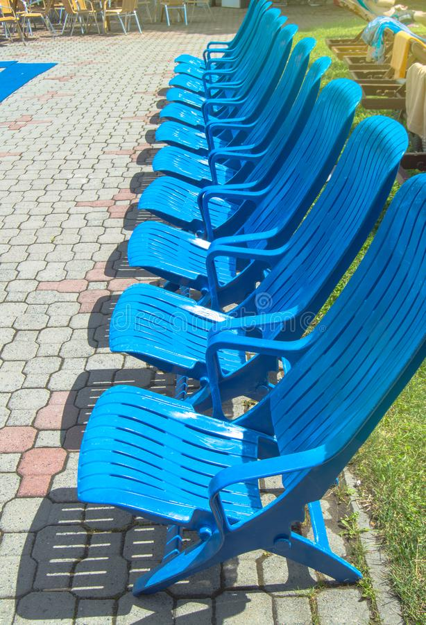 Summer recreation area by the outdoor pool, modern empty plastic blue sun loungers stand in a row on the paving slabs on a hot royalty free stock photo