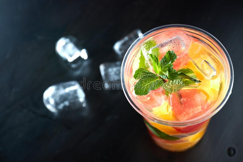 Summer refreshing cocktails with citrus and mint. orange and grapefruit segments. drink on a black table with ice cubes. close-up stock photography