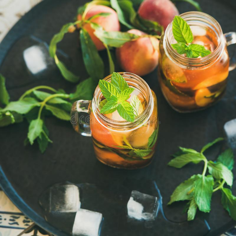 Summer refreshing cold peach ice tea in jars, square crop stock image
