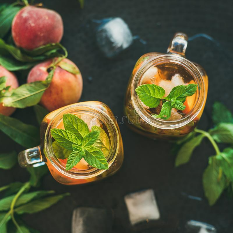 Summer refreshing cold peach ice tea in jars, square crop royalty free stock photo