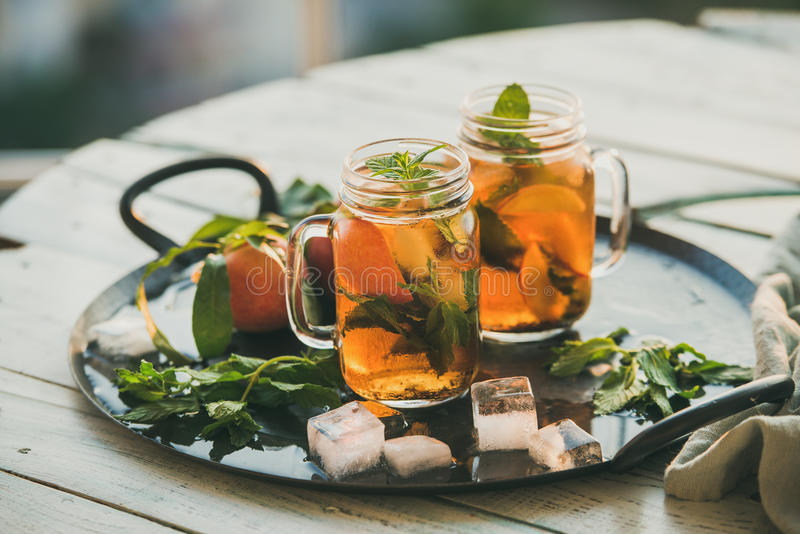 Summer refreshing cold peach ice tea on wooden table royalty free stock photos