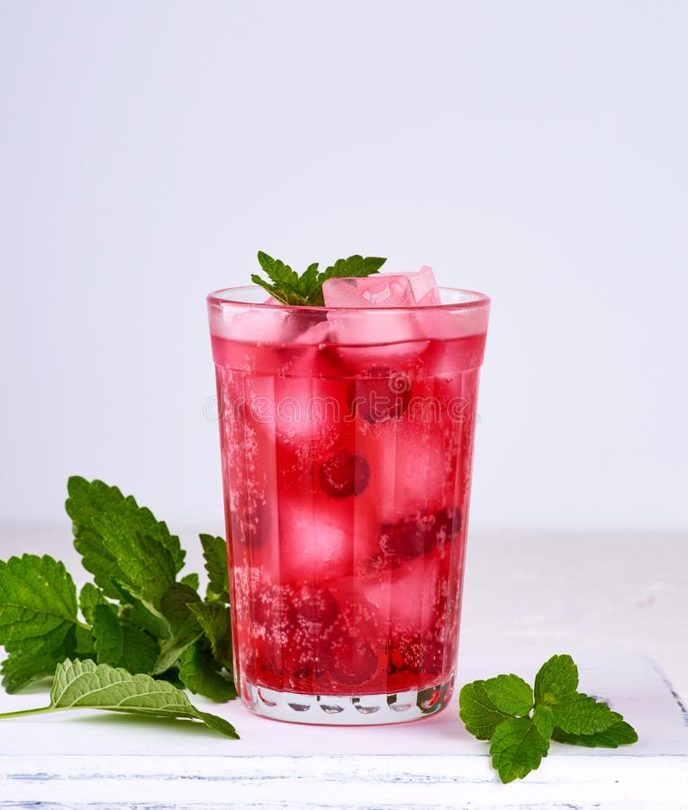 summer refreshing drink with berries of cranberries and pieces of ice in a glass royalty free stock photo