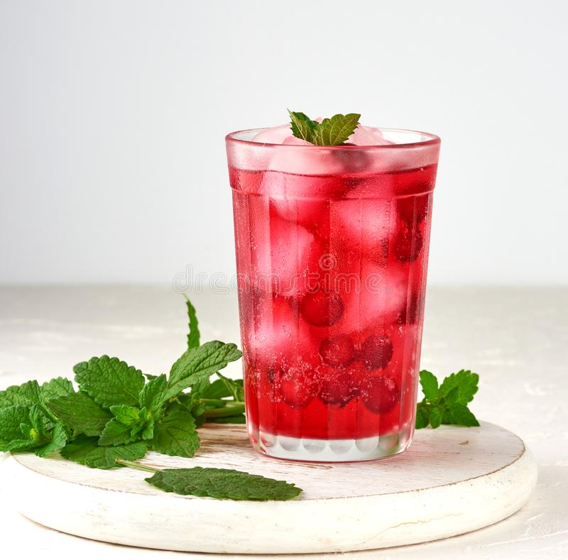 summer refreshing drink with berries of cranberries and pieces of ice in a glass royalty free stock photos