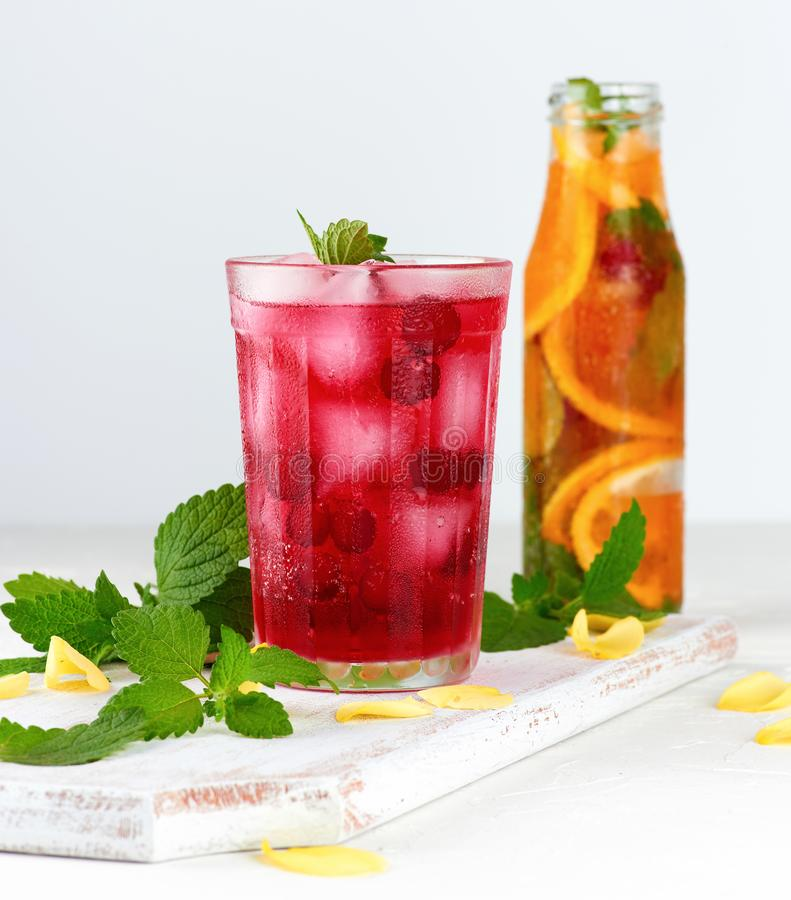 summer refreshing drink with berries of cranberries and pieces of ice in a glass royalty free stock image