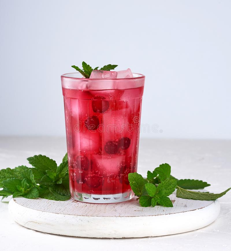 summer refreshing drink with berries of cranberries and pieces of ice stock image