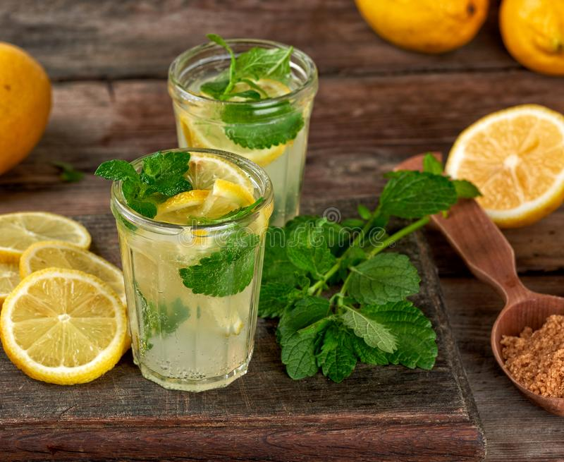 summer refreshing drink lemonade with lemons, mint leaves in a glass stock photos