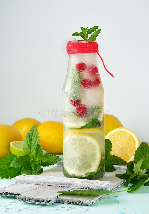 Summer refreshing drink lemonade with lemons, mint leaves, lime in a glass bottle. Summer refreshing drink lemonade with lemons, cranberry, mint leaves, lime in royalty free stock photos