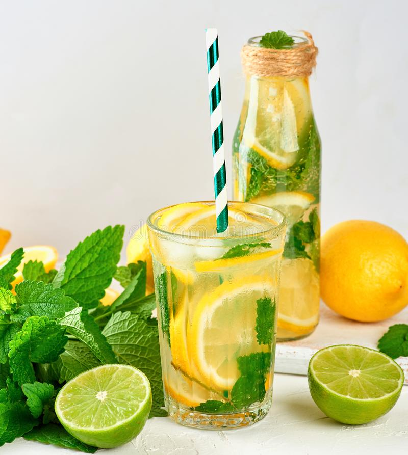 summer refreshing drink lemonade with lemons, mint leaves, lime in a glass bottle royalty free stock image