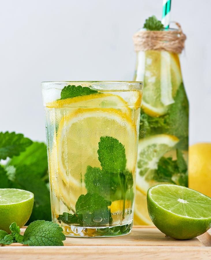 summer refreshing drink lemonade with lemons, mint leaves, lime in a glass stock photos
