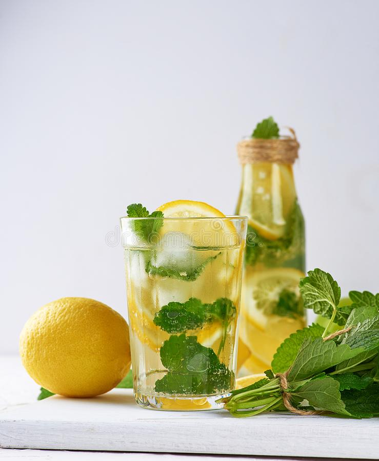 summer refreshing drink lemonade with lemons, mint leaves, lime in a glass stock images