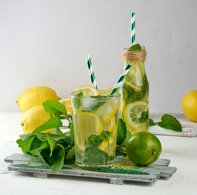 summer refreshing drink lemonade with lemons, mint leaves, lime in a glass royalty free stock photo