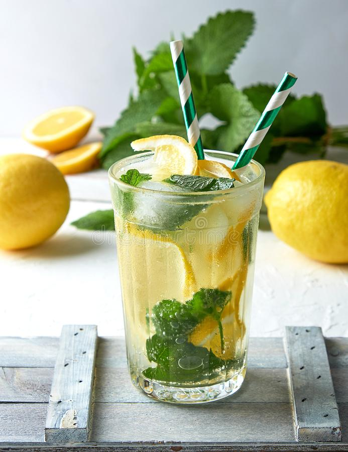 summer refreshing drink lemonade with lemons, mint leaves, lime in a glass stock photography