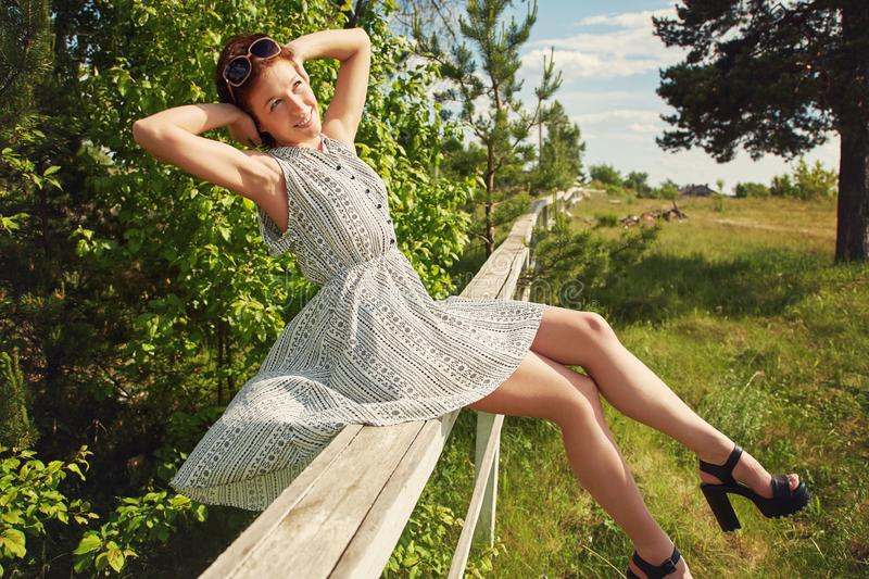 Summer relax rustic portrait of a young woman sitting on fence in countryside. stock photography