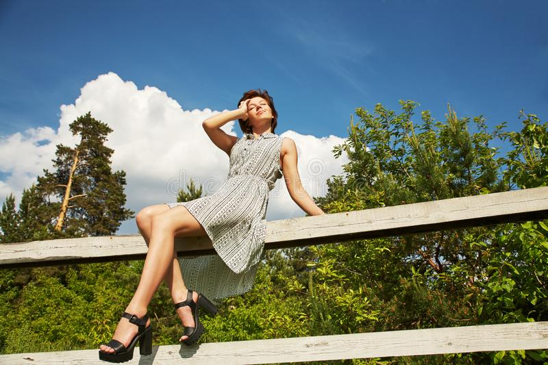 Summer relax rustic portrait of a young woman sitting on fence in countryside. stock images
