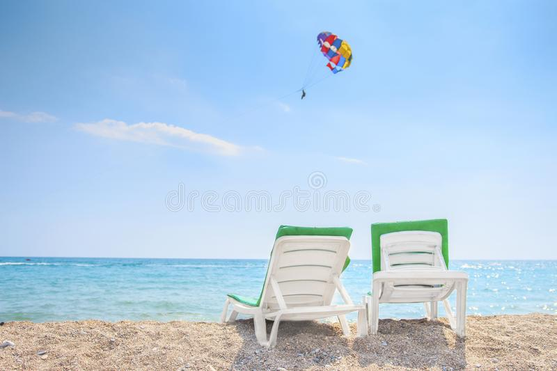 Summer rest background. Two deck chairs on sea beach on clear sunny day. Relax on the beach. Tropical resort concept stock photo